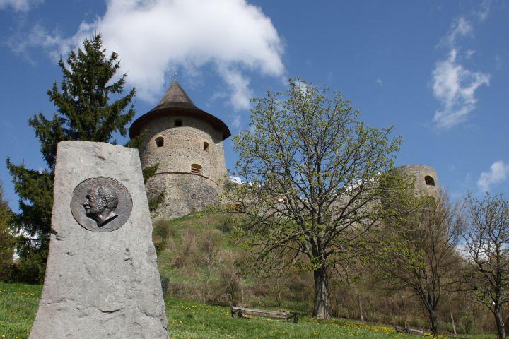 """3100.hu Fotó: A """"Krepuska Géza emlékoszlopot"""" 2001-ben állították, az andezit – bronz művet Molnár Péter készítette. Az emlékoszlop (a közigazgatásilag Salgótarjánhoz tartozó) Somoskőben, a Petőfi-kunyhó alatt, a Somoskő Váralja Emlékparkban található, míg a háttérben látható Somoskő vára már Szlovákia területén áll"""