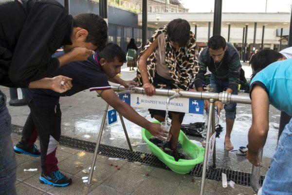 Illegális bevándorlók mosakodnak a tranzitzónában a budapesti Keleti pályaudvarnál 2015. augusztus 21-én (MTI Fotó: Koszticsák Szilárd)