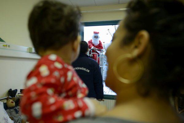 Emelőkosárban érkezik a tűzoltó Mikulás a Szent Lázár Megyei Kórház gyermekosztályára (MTI Fotó: Komka Péter)