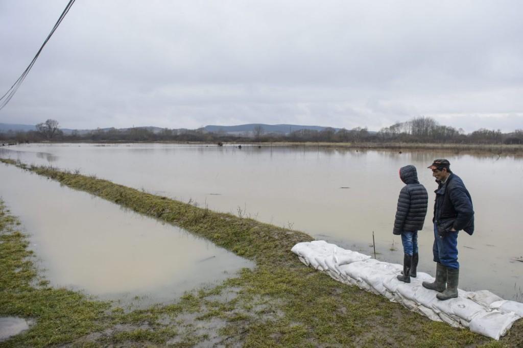 Helyi lakosok az áradó Ipoly folyó mellett Ipolytarnócon (MTI Fotó: Komka Péter)