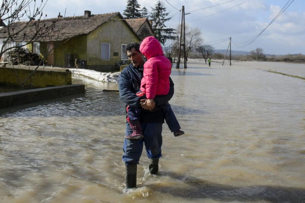 Bada Tibor unokáját viszi karjában az Ipoly folyó által elárasztott Rákóczi utcában Ipolytarnócon (MTI Fotó: Komka Péter)