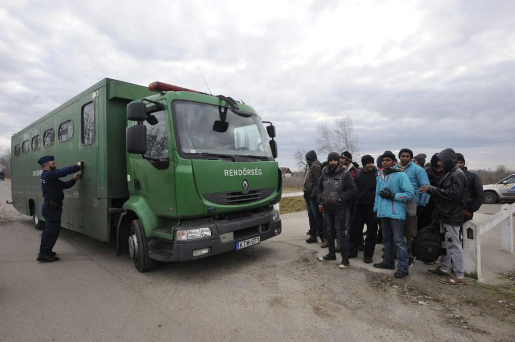 Elfogott határsértők készülnek felszállni egy rendőrségi járműre Röszke térségében 2016. február 9-én. Ezen a napon 24, magát pakisztáni, indiai és nepáli állampolgárnak valló férfit fogtak el egy csoportban, miután a határzárat megrongálva illegálisan magyar területre léptek. (MTI Fotó: Kelemen Zoltán Gergely)