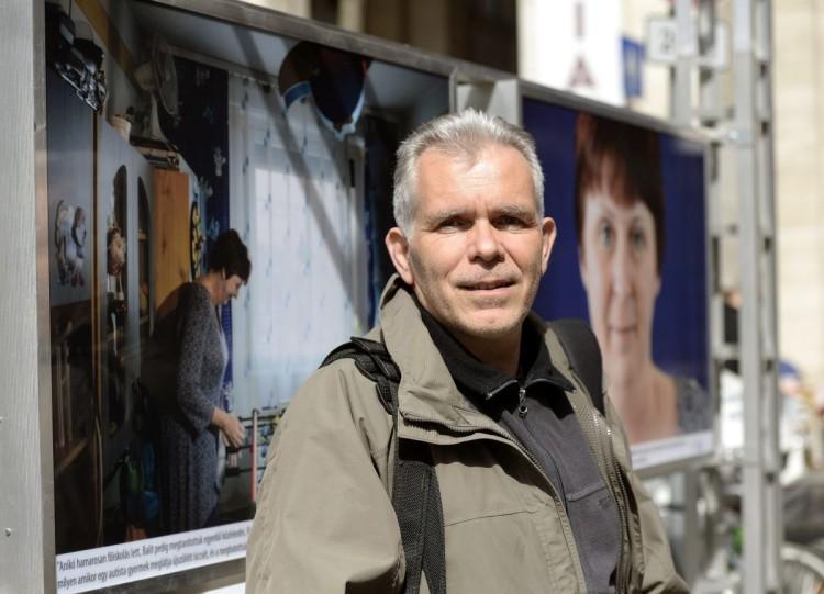 Komka Péter, az MTI/MTVA fotóriportere, képei előtt a Nők kékben című szabadtéri fotókiállításon (MTI Fotó: Bruzák Noémi)