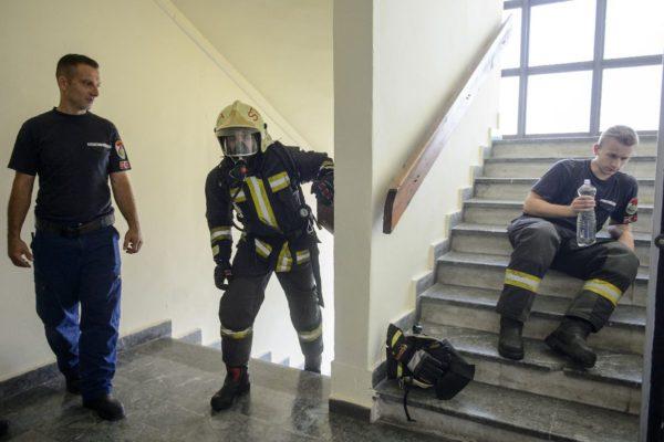Egy tűzoltó célba ér, egy másik már pihen a lépcsőfutó verseny céljában, a 18 emeletes garzonházban (MTI Fotó: Komka Péter)