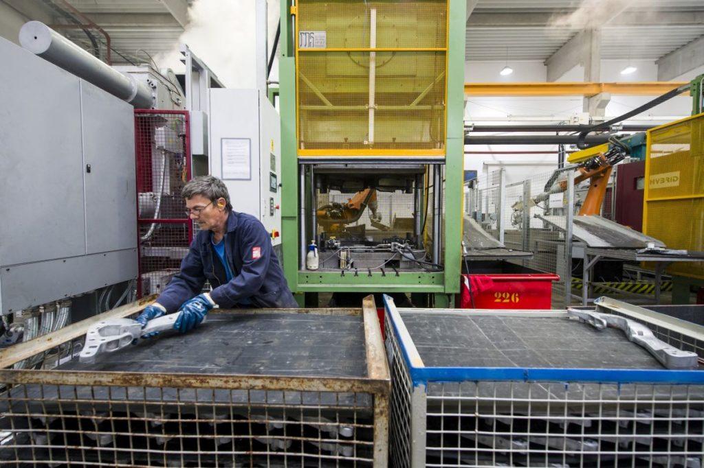 Egy dolgozó a présgépből kikerült munkadarabot pakolja a CSABAcast apci új üzemében (MTI Fotó: Komka Péter)