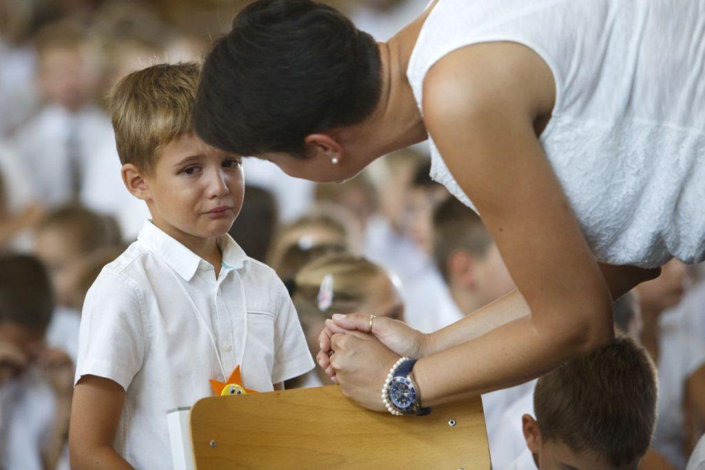 Elsős diákot vígasztal tanítója a nemzeti tanévnyitón a sárvári Nádasdy Tamás Általános Iskolában (Fotó: MTI/Varga György)