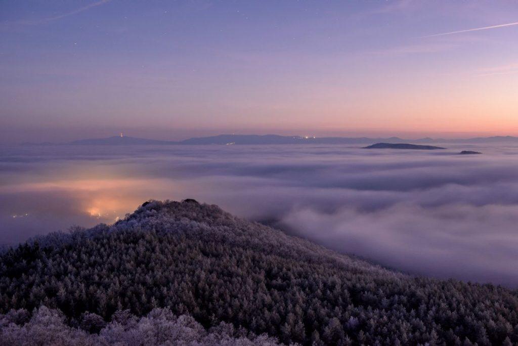 Az előtérben a Kis-Salgó, a háttérben a Mátra, a köd fölé magasodó Salgó várából fotózva (Fotó: MTI/Komka Péter)