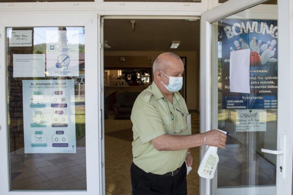 A bejárati ajtót fertőtleníti a szavazatszámláló bizottság tagja a vizslási időközi önkormányzati választáson (Fotó: MTI/Komka Péter)