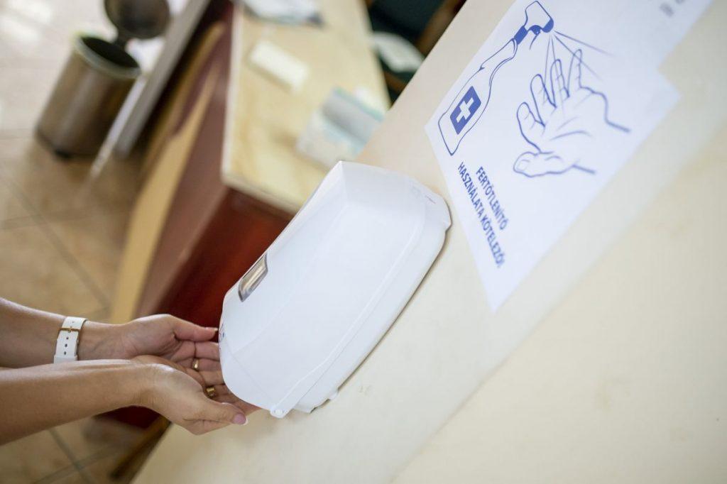Kezét fertőtleníti egy szavazó a vizslási időközi önkormányzati választáson, a közösségi házban kialakított szavazókörben (Fotó: MTI/Komka Péter)