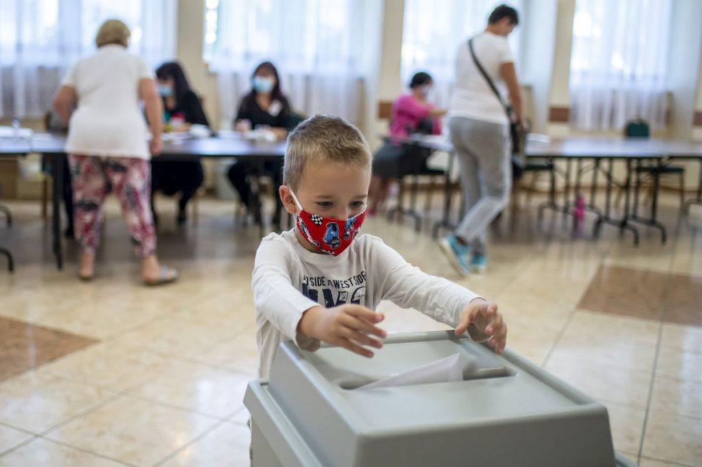 Egy fiú bedobja édesanyja szavazatát a vizslási időközi önkormányzati választáson, a közösségi házban kialakított szavazókörben (Fotó: MTI/Komka Péter)