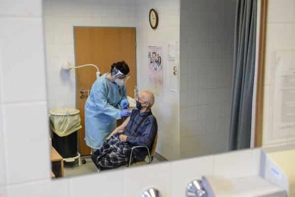 Almásyné Bakos Eszter szakápoló a Pfizer-BioNTech koronavírus elleni vakcinájának második adagjával olt be egy idős férfit a salgótarjáni Szent Lázár Megyei Kórház oltópontján 2021. február 27-én (Fotó: MTI/Komka Péter)