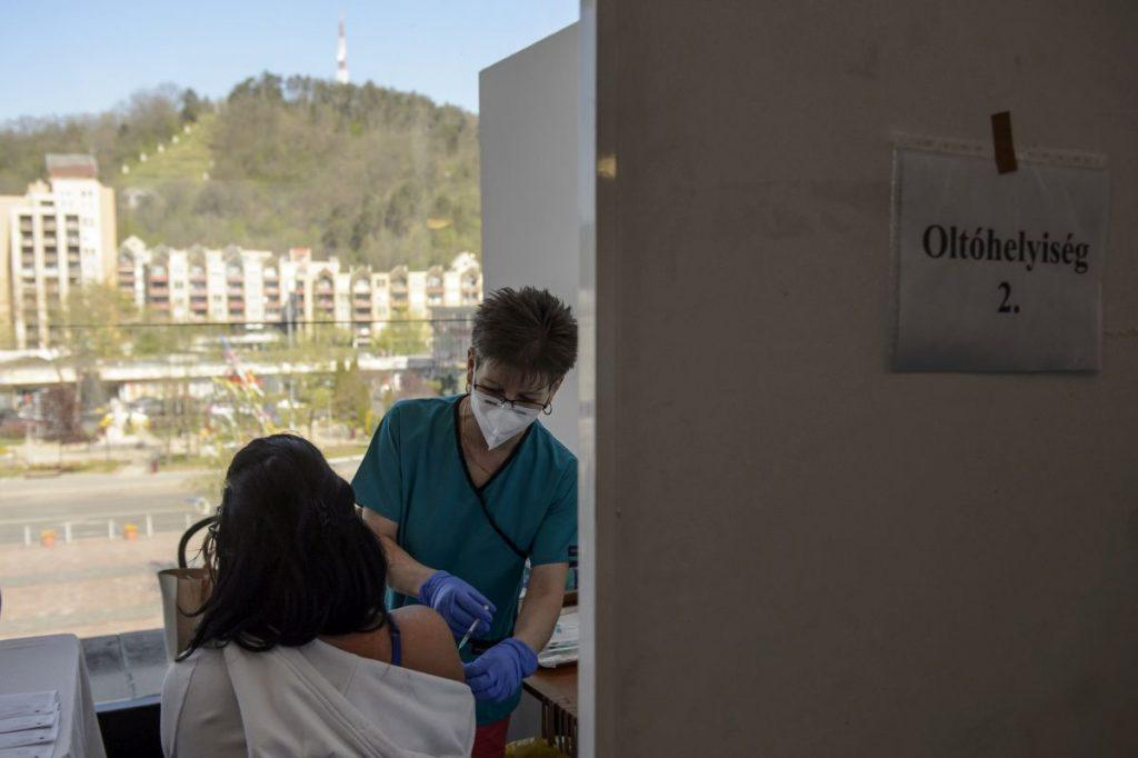 Beoltanak egy nőt a német-amerikai fejlesztésű Pfizer-BioNTech koronavírus elleni oltóanyag, a Comirnaty-vakcina első adagjával a salgótarjáni József Attila Művelődési Központban kialakított oltóponton 2021. május 1-jén (Fotó: MTI/Komka Péter)
