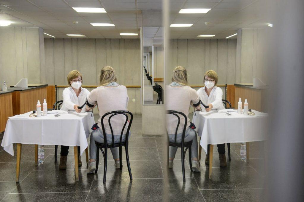 Megmérik egy nő vérnyomását, mielőtt beoltják a német-amerikai fejlesztésű Pfizer-BioNTech koronavírus elleni oltóanyaggal, a Comirnaty-vakcinával a salgótarjáni József Attila Mûvelődési Központban kialakított oltóponton 2021. május 1-jén (Fotó: MTI/Komka Péter)