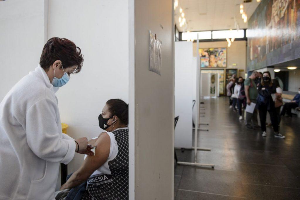 Beoltanak egy nőt a német-amerikai fejlesztésű Pfizer-BioNTech koronavírus elleni oltóanyag, a Comirnaty-vakcina első adagjával a salgótarjáni József Attila Mûvelődési Központban kialakított oltóponton 2021. május 1-jén (Fotó: MTI/Komka Péter)