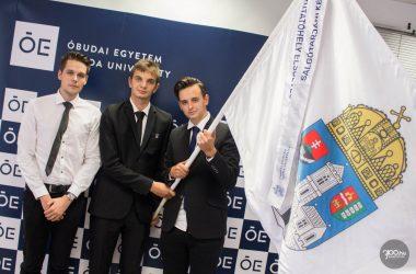3100.hu Fotó: Az Óbudai Egyetem újdonsült hallgatóinak képviselői az egyetem zászlójával a Salgótarjáni Képzési Központ és Kutatóhely ünnepélyes tanévnyitóján, 2019. szeptember 9-én